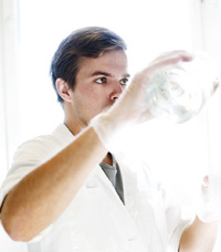 Man in a lab coat holding a bottle